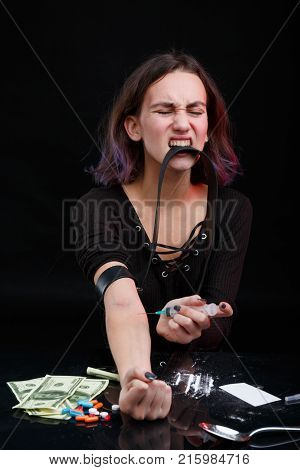 A young girl is a drug addict, holds a black tourniquet with her teeth and clamps her hand, and injects a dose of the drug in her hand. The poison on the tablets tablets, cocaine powder, dollar bills and syringes. On a black background.
