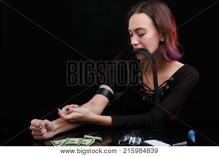 A young girl, a drug addict pinches the veins with a black tourniquet and injects a dose of drugs with a syringe. Next to the table are dollar bills, scattered cocaine powder and a used syringe.
