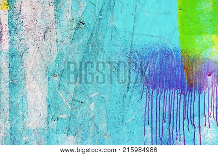 Close-up of abstract dirty painted wooden surface, flowing paint of different bright colors, as graffiti. Colorful grunge texture of wall. Abstract modern background, pattern, wallpaper, banner design