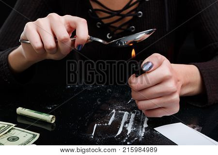 Hands girl addicts heats the drug in a spoon with a lighter over a table with scattered cocaine, twisted dollar bills, a blade and cards. On a black background.