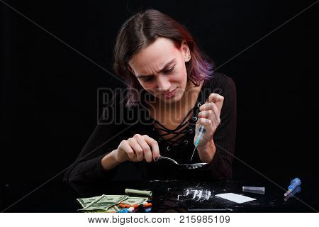 A young drug-dependent girl picks up a dose of a drug in a syringe from a spoon above the table with scattered cocaine powder, narcotic tablets and dollar bills. On a black background.