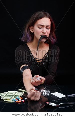 A young drug-dependent girl injects a syringe with a dose of drugs into her arm, pulling the veins in a dense black bundle. Next to the table are narcotic tablets, scattered cocaine powder and dollar bills. On a black background.