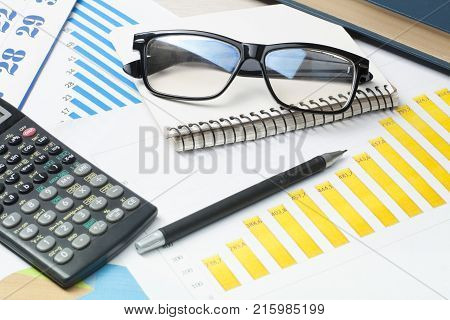 Home savings, budget concept. Chart, notepad, pen, calculator and glasses on wooden table