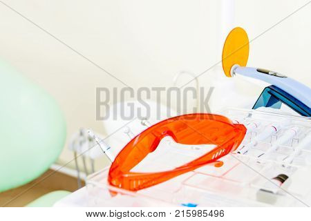 Dentist workplace in clinic. Modern tools equipment of dentist: uv glasses uv tool for dentist sealants and treatments teeth