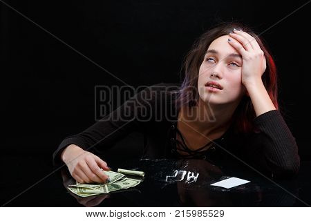 A drug addict young girl, under the narcotic effect of cocaine, sits at a table, her eyes are upside down. Near the table scattered cocaine on a few dollar bills. On a black background.