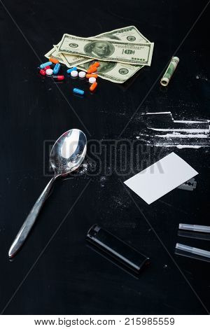 On a black background, a few dollar bills, scattered cocaine powder, narcotic tablets, a metal spoon and a black lighter.