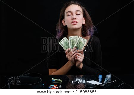 A young drug-dependent girl holding several dollar bills, next to her on the table scattered cocaine powder, pills and syringes. On a black background.