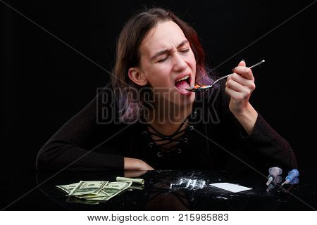 A drug addict girl swallows a bunch of colored tablets from a spoon, alongside a scattered powder of cocaine, dollar bills and syringes. On a black background.