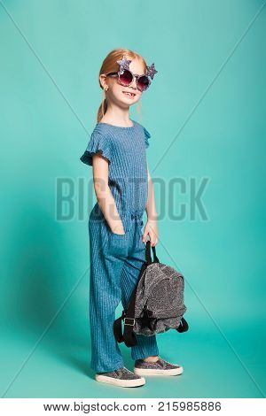 isolated on blue, smiling red-haired girl in star-shaped sunglasses, blue overall and silver slip ons, holding a lustrous backpack. one hand is in her pocket. copyspace.