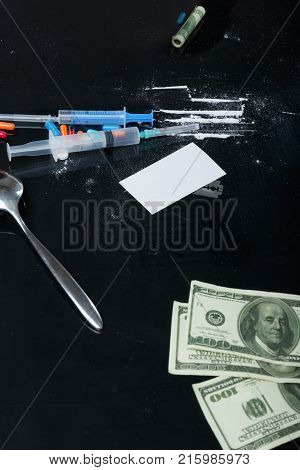 On the black table scattered cocaine powder, dollar bills, a metal spoon and syringes.