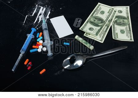 On a black table, cocaine powder, strips of cocaine, dollar bills, colored tablets, a metal spoon and syringes.