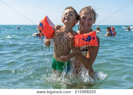 Young mother and smiling baby boy son in green baseball cap playing in the sea in the day time. Positive human emotions feelings joy. Spring and summer holidays.