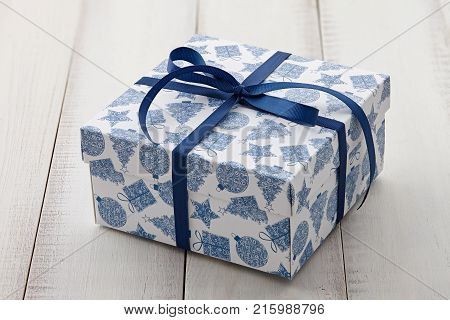 Christmas gift or present box with a blue holiday print tied with ribbon on white wooden background