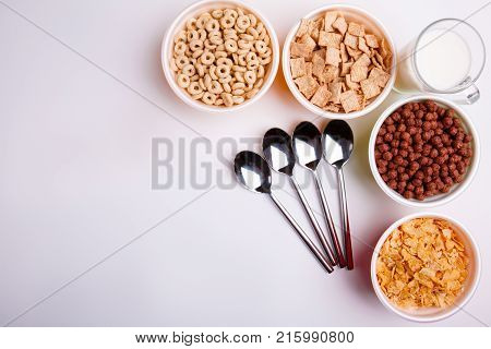 Close-up of different types of cereal in different plates, with four spoons, in the upper right corner is milk, rings, cereal, balls, pads on a white background.