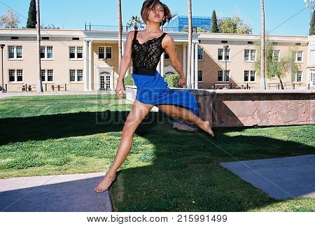 A lovely Asian female model jumping outdoors