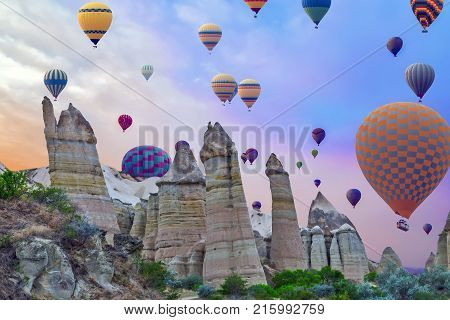 Hot Air Balloons Flying In Sunset Mountain Landscape In Cappadocia, Goreme National Park, Turkey.