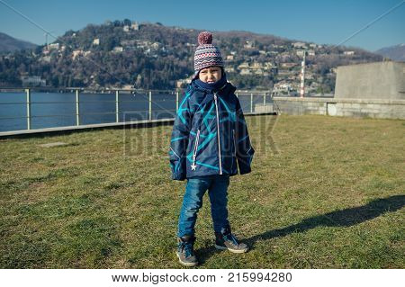 Young boy standing on the grass near the lake and makes faces