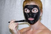 Girl in a cosmetic black mask. Cleansing mask of aspirin and activated carbon. Black cosmetic face mask poster