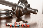 Steroid pills with dumbbell waight in the background - doping in sport. poster