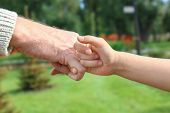 Senior man and his grandchild making pinky promise on blurred background poster