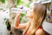 Tired female tourist with closed eyes drinking water outdoors. Calm young woman enjoying refreshing drink during stifling heat. Thirsty concept poster