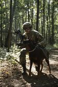 Picture of soldier in helmet with submachine gun and dog on task in forest poster
