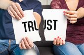 No trust. Cheating infidelity marital problems having an affair and another partner betrayal mistrust or being unfaithful concept. Couple man and woman ripping same paper. poster