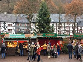 Monschau, Germany - December 17, 2016: German Christmas Market. Shoppers visit vendors selling gifts, wine and gourmet food at the annual Monschau Christmas market.