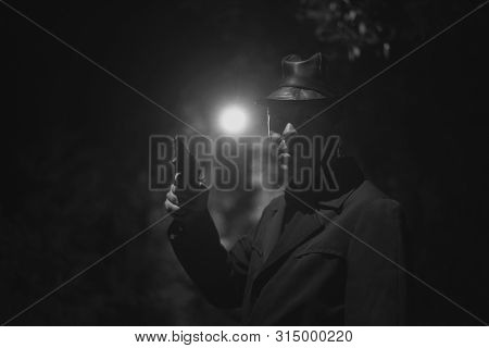 Thrilled Detective Agent In A Leather Hat And Coat Is Standing And Looking Into The Dark With A Hand