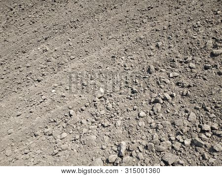Full Frame View Of Plowed Agriculture Field Naked Light Brown Soil With Rotary Blade Tracks.