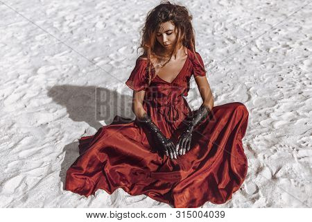 Beautiful Young Fashionable Woman In Elegant Dress Sitting On Sand At Sunset