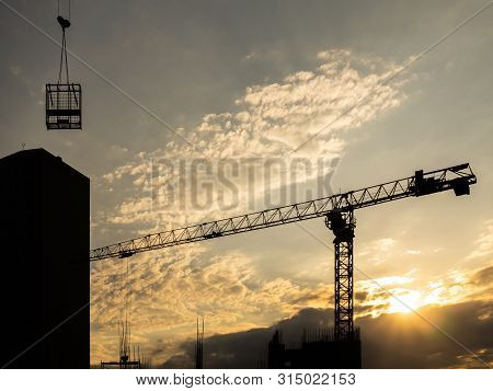 Construction Crane With Cargo. Silhouette Of A House And A Crane. Construction At Sunset. Constructi