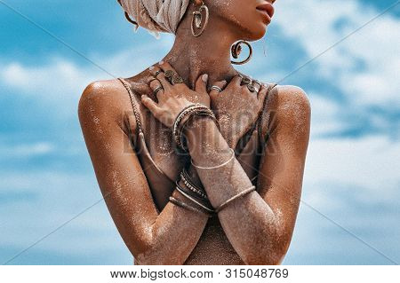Close Up Portrait Of Beautiful Young Tribal Woman At Dramatic Sky Background
