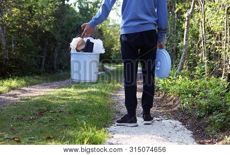 Youngster Is Holding Plastic Bucket On The Forest Path For Plastic Bottles And Trash.