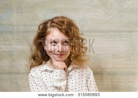 A Teenager With A Sly Look. The Girl Is Up To Something. Conceived Girl. Portrait Of A Teenage Girl.