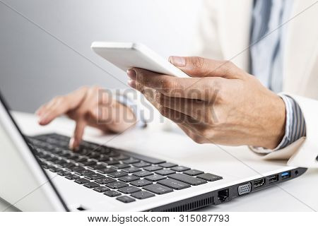 Man In Business Suit Holding Smartphone And Typing At Laptop Computer. Side View Shot Of Businessman
