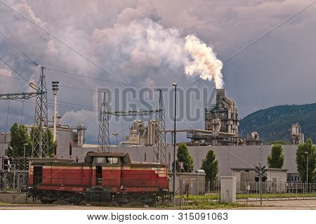 Industrial Scene, Smokestack, Smoke, Train,pipes And Electric Pylons.