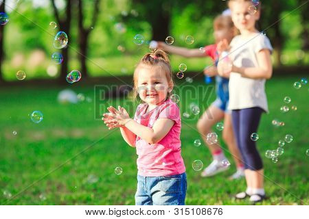 The Group Of Children Blowing Soap Bubbles.