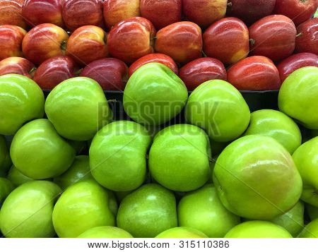 Gala (red) and Granny Smith (green) apples in a fruit bin display for sale. Gala apples have a mild and sweet flavor. Granny Smith apples are famously green apples with a tart flavor popular for pies. poster