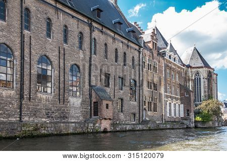 Gent, Flanders, Belgium -  June 21, 2019: Brown Stone University Building Het Pand Bordering Leie Ri