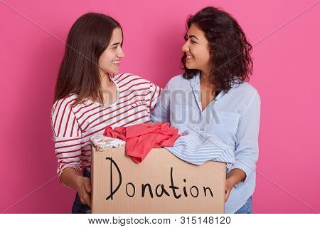 Close Up Portrait Of Two Girls Volunteering, Women Holding Box With Clothes For Poor People, Attract