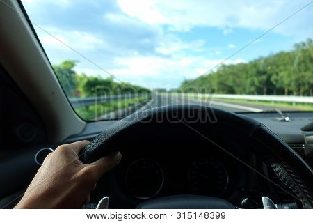 Inside View, Hand Of A Driver On Steering Wheel Of A Car With Empty Asphalt Road Background. High-qu