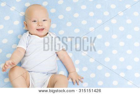 Happy Baby Boy, Smiling Infant Kid Portrait, Five Months Old Child Lying On Back On Blue Background