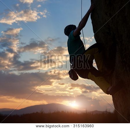 Silhouette of man climbing on rock. Climber training on natural relief. Extreme sport. Active recreation in nature. Overcoming difficult climbing route. Amazing sunrise sky over mountains in twilight poster