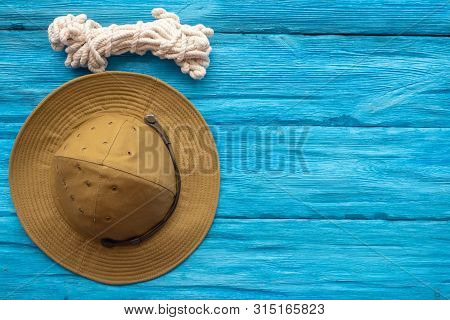 Tourist Hat And A Rope Hank On A Traveler Blue Wooden Table Background With A Copy Space.