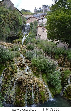 Wonderful Waterfalls With Silk Effect Of A Crystalline Greenish Water Running Between The Houses And