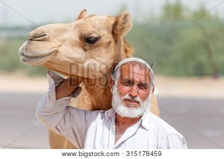 Al Ain, Uae - March 27, 2019: Man Selling Hay Stacks On The Side Of The Road Near Al Ain, Uae Posing