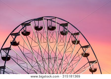 Ferris Wheel At The Fair During The Picturesque Sunset