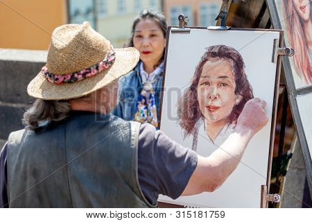 Prague, Czech Republic - May 8, 2019: Street Artist Creating His Art Painting Portrait Of A Woman In