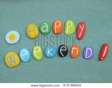 Happy Weekend Text Composed With Multi Colored Stones Over Green Sand